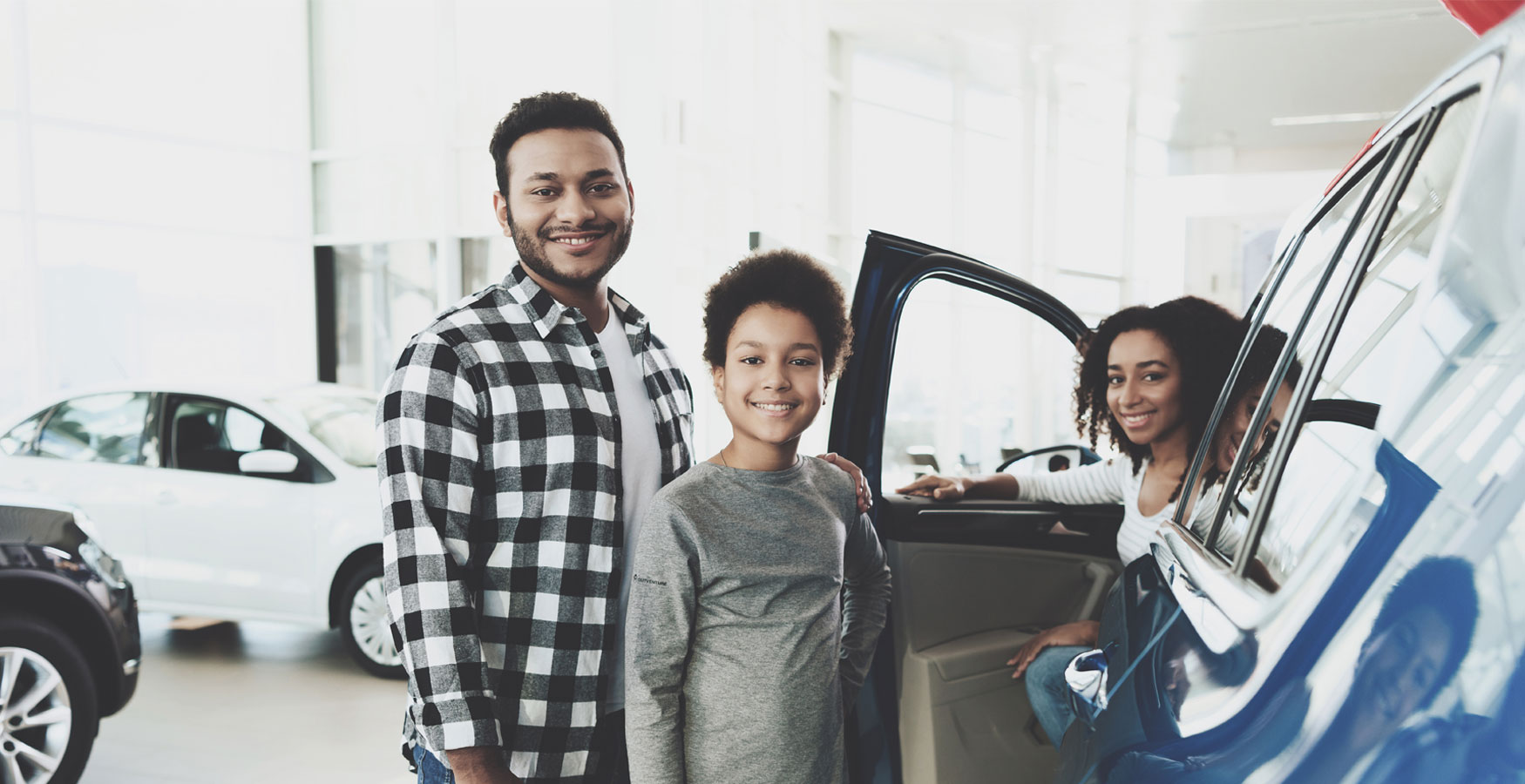 Family standing next to their new car in dealership.
